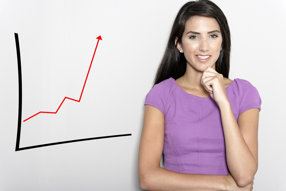 Professional working woman in corporate purple dress, with a concept graph displaying an increase..jpeg