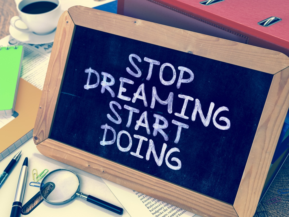 Stop Dreaming Start Doing. Motivational Quote Hand Drawn on Chalkboard on Working Table Background. Blurred Background. Toned Image.